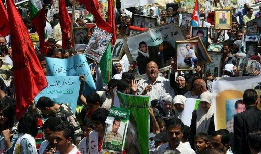 "Palestinians hold pictures of incarcerated relatives during a rally in the West Bank city of Nablus, May 8, in solidarity with prisoners on hunger strike. UN chief Ban Ki-moon urged Israel to try or release hunger-striking Palestinian prisoners after activists denounced his ""silence"" in a protest outside the UN's West Bank offices"