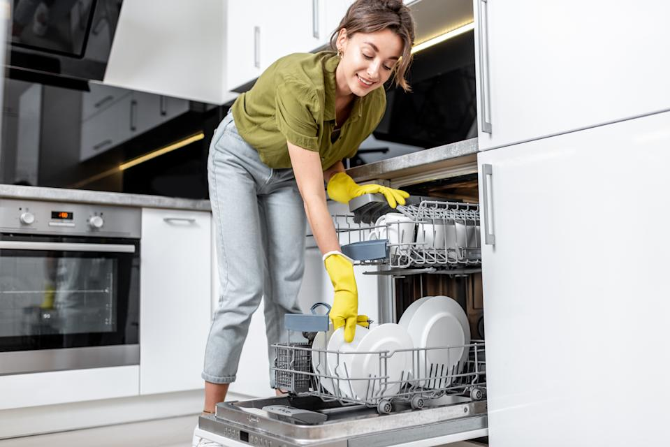 Young woman loading dishes into the dishwasher machine. Easy housework with kitchen appliances concept