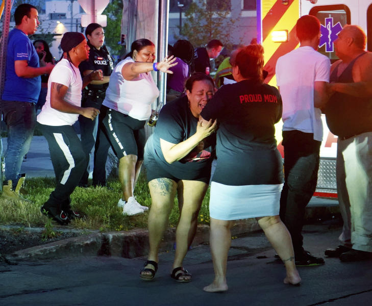 A woman reacts as emergency response crews move wounded people to ambulances after multiple people were shot at a party Saturday, June 20, 2020, in Syracuse, N.Y. Nine people were shot and one victim, a 17-year-old boy, was in critical condition Sunday. (Ellen M. Blalock/Syracuse Post-Standard via AP)