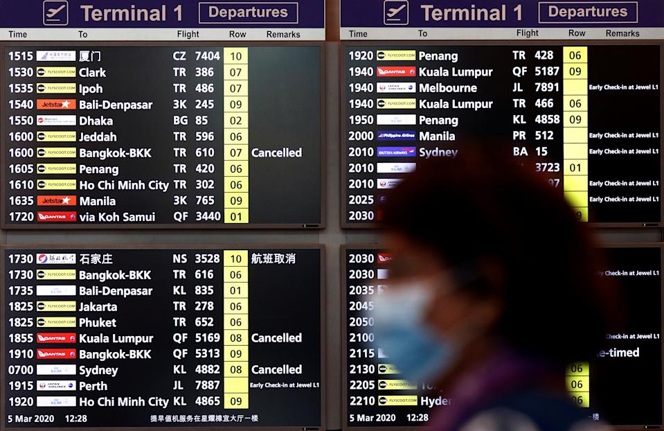 A woman wearing a mask passes a flight information board at Changi Airport in Singapore March 5, 2020. REUTERS/Edgar Su
