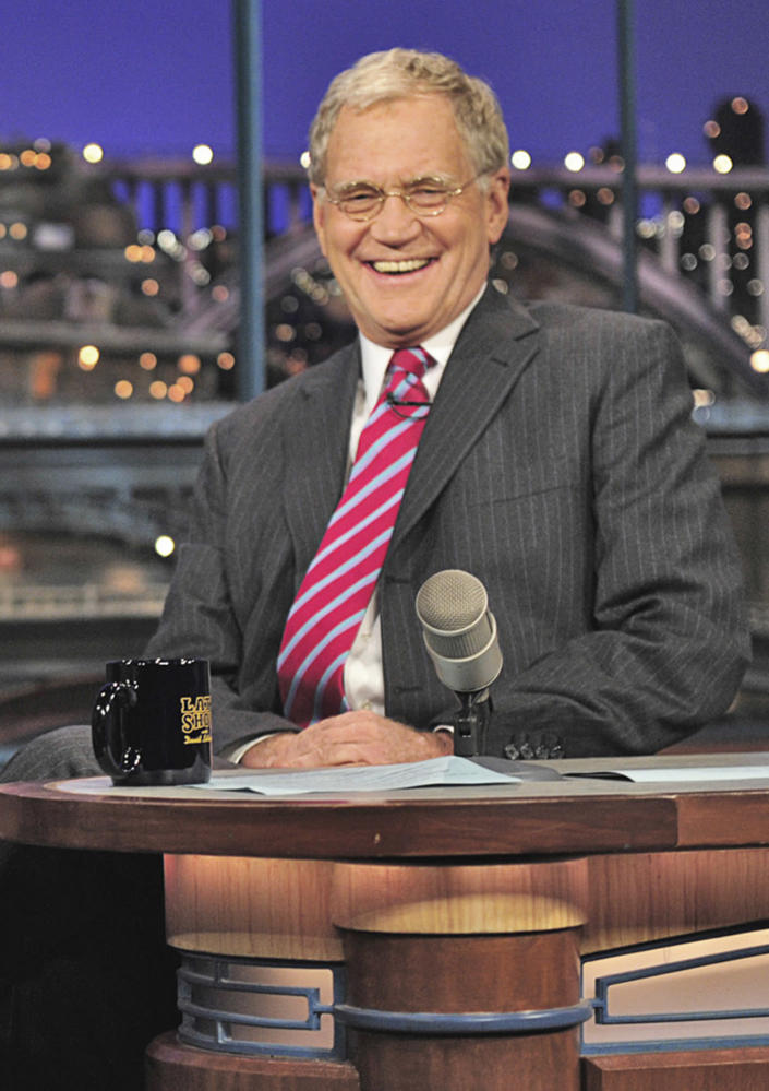 """In this Nov. 23, 2010 file photo released by CBS, host David Letterman smiles on the set of """"The Late Show with David Letterman, in New York. CBS announced Tuesday, April 3, 2012 that both Letterman and Craig Ferguson have re-upped to keep hosting their respective hours _ """"Late Show"""" and """"The Late Late Show"""" _ through 2014.(AP Photo/CBS, John Paul Filo) MANDATORY CREDIT; NO SALES; NO ARCHIVE; NORTH AMERICAN USE ONLY"""