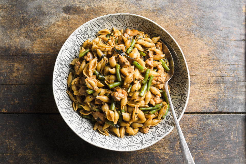 This image released by Milk Street shows a recipe for harissa-spiced pasta with chicken and green beans. (Milk Street via AP)