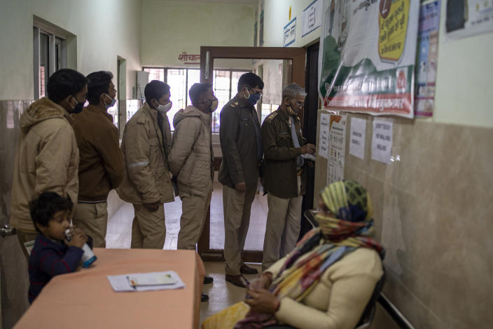 Police officers wait for their turn to receive COVID-19 vaccine at a health centre in Greater Noida, a suburb of New Delhi, India, Thursday, Feb. 11, 2021. When the coronavirus pandemic took hold in India, there were fears it would sink the fragile health system of the world's second-most populous country. Infections climbed dramatically for months and at one point India looked like it might overtake the United States as the country with the highest case toll. But infections began to plummet in September, and experts aren't sure why .(AP Photo/Altaf Qadri)