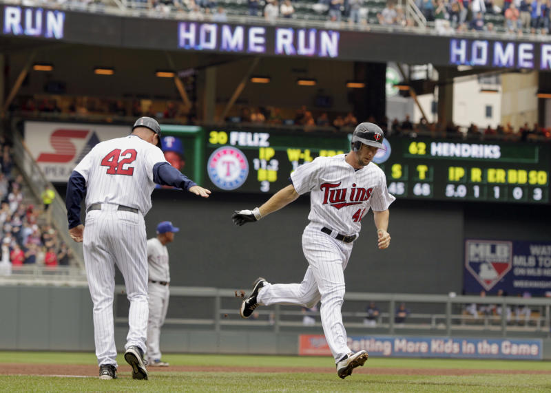 Minnesota Twins' Clete Thomas is congratulated by third base coach Steve Liddle, left, as he runs toward home plate on a two-run home run against Texas Rangers pitcher Neftali during the fifth inning of a baseball game on Sunday, April 15, 2012, in Minneapolis. The players were all wearing No. 42 jerseys in honor of Jackie Robinson Day. (AP Photo/Genevieve Ross)