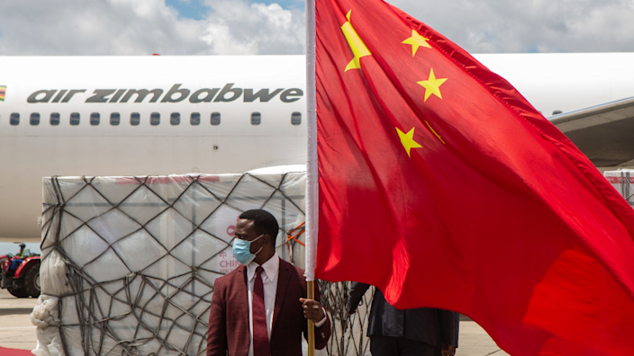A man holds a Chinese flag in front of the shipment of Sinovac and Sinopharm vaccines at Harare International Airport, Zimbabwe - March 2021