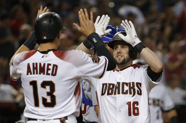 Arizona Diamondbacks' Chris Owings (16) celebrates his two-run home run against the Chicago Cubs with Nick Ahmed (13) during the sixth inning of a baseball game Wednesday, Sept. 19, 2018, in Phoenix. (AP Photo/Ross D. Franklin)