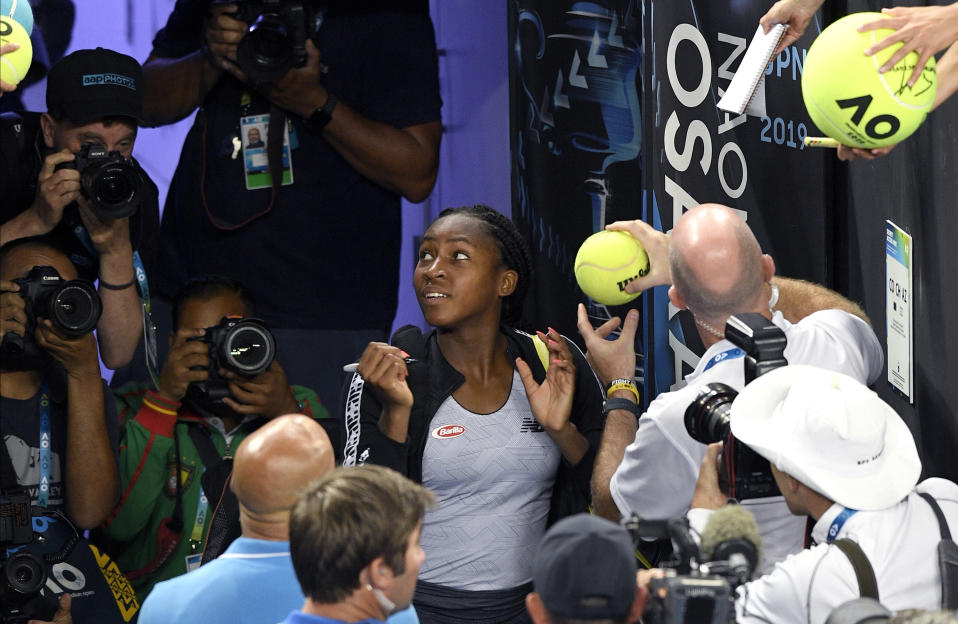 """United States' Cori """"Coco"""" Gauff signs autographs after defeating compatriot Venus Williams during their first round singles match at the Australian Open tennis championship in Melbourne, Australia, Monday, Jan. 20, 2020. (AP Photo/Andy Brownbill)"""