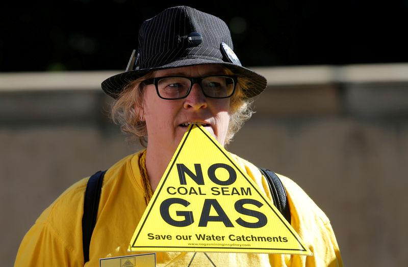 FILE PHOTO: A protester against coal seam gas mining in the Pilliga region of rural Australia holds a placard between her teeth outside the venue of the Committee for Economic Development of Australia (CEDA) meeting in Sydney