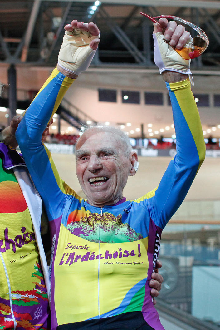 French cyclist Robert Marchand aged 102, celebrates after beating his record for distance cycled in one hour, at the velodrome of Saint-Quentin en Yvelines, outside Paris, Friday, Jan. 31, 2014. The 102-year-old broke his own world record in the over-100s category Friday, riding 26.927 kilometers (16.7 miles) in one hour, more than 2.5 kilometers better than his previous best time in the race against the clock two years ago. (AP Photo/Thibault Camus)