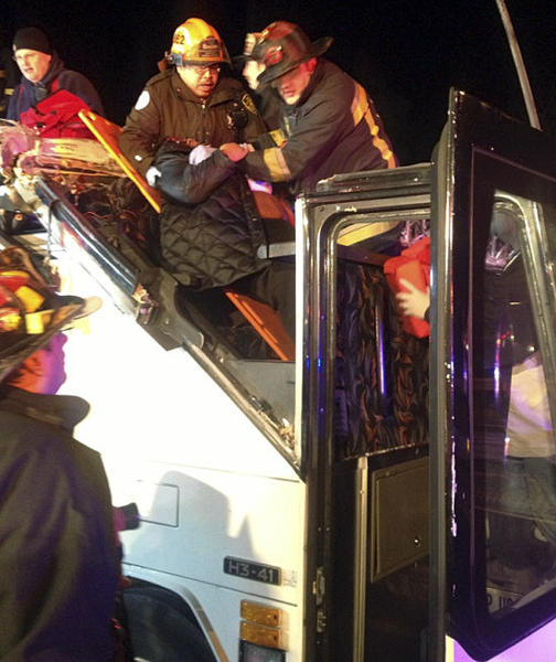 In this photo released by the Boston Fire Department via Twitter, firemen work to remove injured passengers from a bus that hit an bridge as it traveled along Soldiers Field Road in the Allston neighborhood of Boston Saturday night, Feb. 2, 2013. Officials said the bus carryinyg 42 people was traveling from Harvard University home to Pennsylvania when it struck the overpass. (AP Photo/Boston Fire Department)