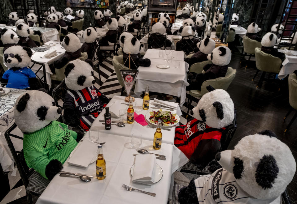 FILE - In this Nov. 24, 2020 file photo, plush pandas and Corona beer bottles decorate the tables of a closed restaurant in Frankfurt, Germany. Restaurants all over Germany were closed as a partial lockdown began in November to avoid the further outspread of the coronavirus. More than 50,000 people have died after contracting COVID-19 in Germany, a number that has risen swiftly over recent weeks as the country has struggled to bring down infection figures. (AP Photo/Michael Probst, File)