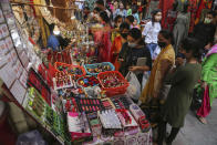 Indians crowd a market area ahead of Hindu festivals in Jammu, India, Sunday, Oct.25, 2020. Weeks after India fully opened up from a harsh lockdown and began to modestly turn a corner by cutting new coronavirus infections by near half, a Hindu festival season is raising fears that a fresh surge could spoil the hard-won gains. (AP Photo/Channi Anand)