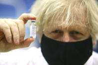 FILE - In this Wednesday, Feb. 17, 2021 file photo, Britain's Prime Minister Boris Johnson holds a vial of the Oxford/Astra Zeneca Covid-19 vaccine at a vaccination centre in Cwmbran, south Wales. The British government says it aims to give every adult in the country a first dose of coronavirus vaccine by July 31, a month earlier than its previous target. In addition, the goal is for everyone over 50 or with an underlying health condition to get a shot by April 15, rather than the previous target of May 1. (Geoff Caddick/Pool via AP, File)