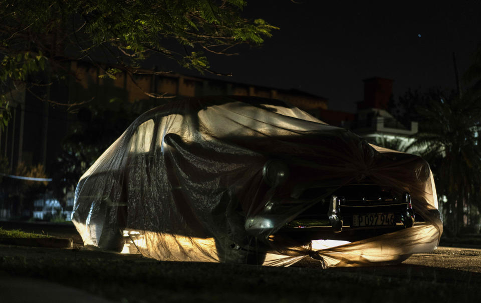 A classic American car is wrapped in plastic to prevent sea salt from corroding it in Havana, Cuba, Tuesday, March 2, 2021. Vintage cars in Cuba are part of daily life with most classic cars being used as taxis and to transport tourists. (AP Photo/Ramon Espinosa)