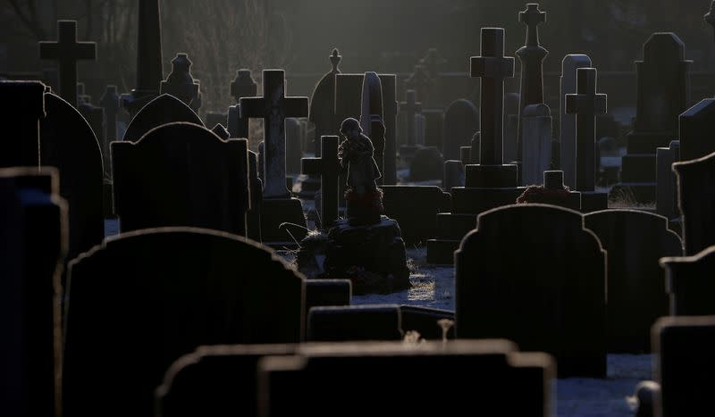 Sunlight hits frost covered headstones in a graveyard amid COVID-19 outbreak in Manchester