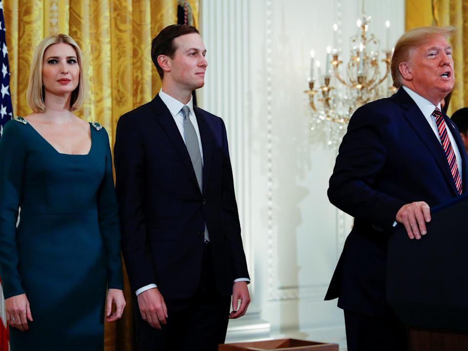 Ivanka Trump and her husband Jared Kushner stand behind then-President Donald Trump as he speaks during a Hanukkah reception at the White House on 11 December, 2019.  (REUTERS)