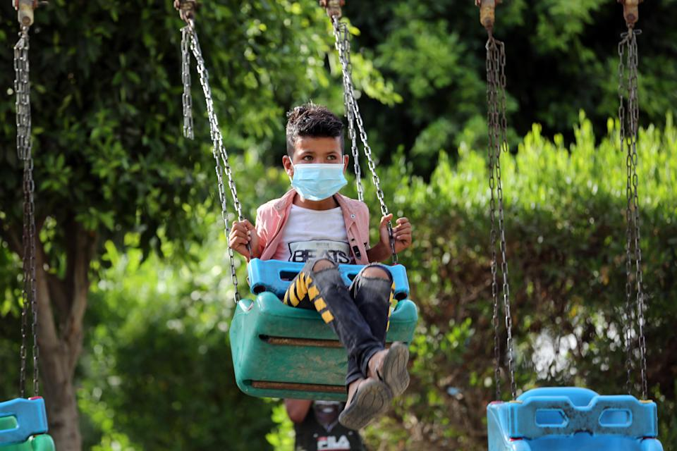 BAGHDAD, May 27, 2020  -- An Iraqi boy wearing a face mask plays on a swing in Baghdad, Iraq, on May 27, 2020. Iraqi Health Ministry on Wednesday said that a total of 5,135 COVID-19 cases were confirmed since the outbreak of the disease in the country, of whom up to 175 have died. (Xinhua via Getty) (Xinhua/ via Getty Images)