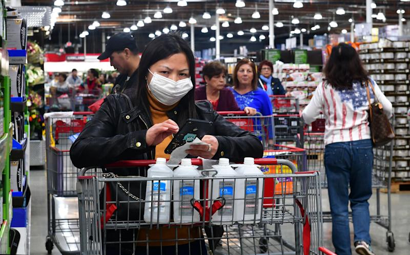 A woman wears a face mask while purchasing bottles of rubbing alcohol at a Costco store in Alhambra, California on February 4, 2020a Home Depot store in Alhambra, California on February 4, 2020. - As the coronavirus outbreak spreads, fueling rumors and misinformation, a petition to cancel all classes in one US school district for fear of the virus has garnered nearly 14,000 signatures. The online petition posted on Change.org urges the Alhambra Unified School District located east of Los Angeles and with a heavily Asian population, to basically shut down until the outbreak is over. School district officials, however, have dismissed the petition as a bid to whip up hysteria over the deadly outbreak that has killed hundreds in China. (Photo by Frederic J. BROWN / AFP) (Photo by FREDERIC J. BROWN/AFP via Getty Images)