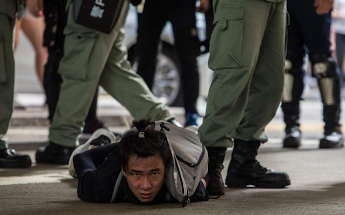 Riot police detain a man during a protest in July 2020 against the new national security law in Hong Kong - DALE DE LA REY/AFP