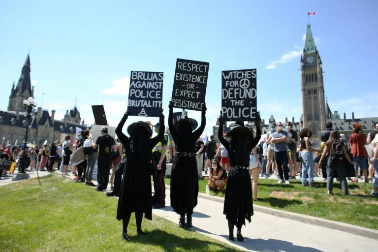 Protestors hold up signs at the Black Lives Matter protest on Parliament Hill in Ottawa (AFP Photo/Dave Chan)