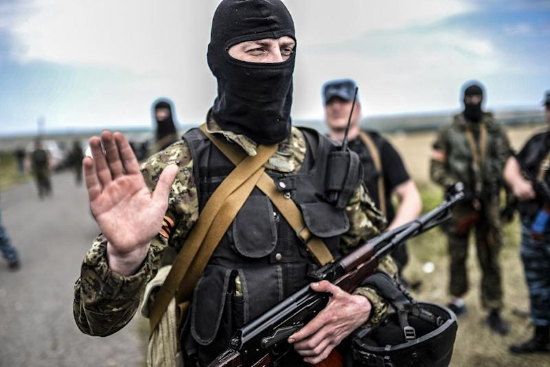 An armed pro-Russian separatist blocks the way to the crash site of Malaysia Airlines Flight MH17, near the village of Grabove, in the region of Donetsk on July 20, 2014