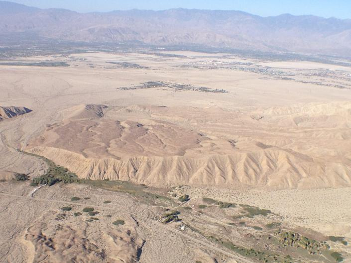 A hilly area where the San Andreas Fault runs through the Coachella Valley is seen from the air. An oasis of palm trees is sustained by water that gushes up along the fault line at the Coachella Valley Preserve.