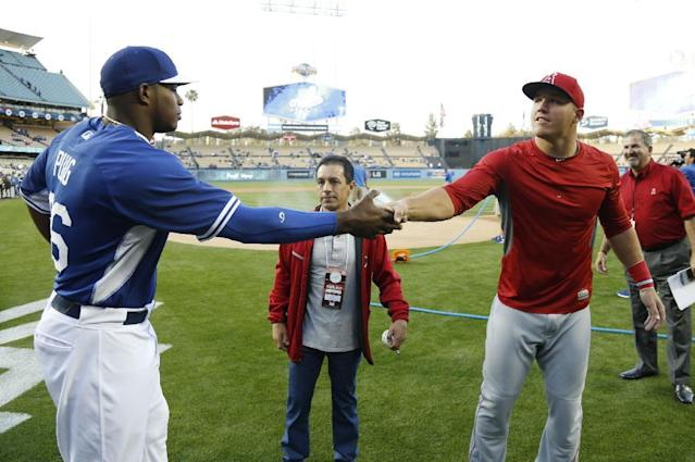 Los Angeles Dodgers' Yasiel Puig, left, shakes hands with Los Angeles Angels' Mike Trout, right, after they talked with jockey Victor Espinoza, center, before Espinoza threw out the first pitch for an exhibition baseball game in Los Angeles, Thursday, March 27, 2014. (AP Photo/Danny Moloshok)