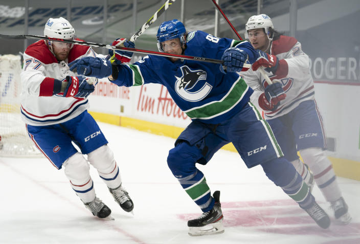 Vancouver Canucks center Jay Beagle (83) is defended by Montreal Canadiens' Brett Kulak (77) and Alexander Romanov (27) during second period NHL action in Vancouver, Wednesday, January 20, 2021. THE CANADIAN PRESS/Jonathan Hayward/The Canadian Press via AP)