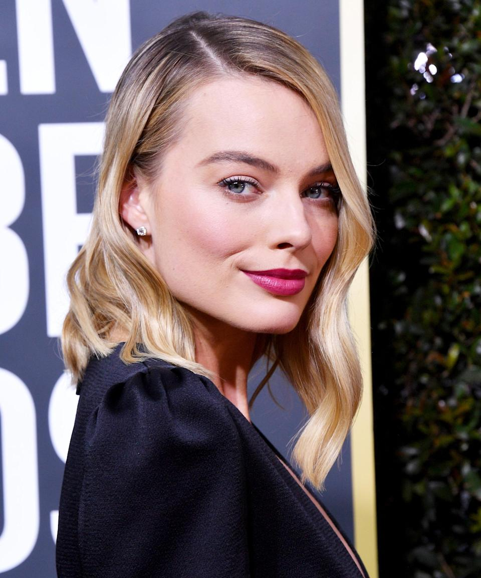 """<h3><strong>Strategic Parting</strong></h3> <br><br>An ode to old Hollywood glam, Scarlett almost always parts Robbie's hair to one side. Paired with a sleek blowout or glossy waves, it shows off her killer bone structure every time. For looser textured looks, they tend to go with a soft center part.<span class=""""copyright"""">Photo: George Pimentel/WireImage..</span><br><br>"""