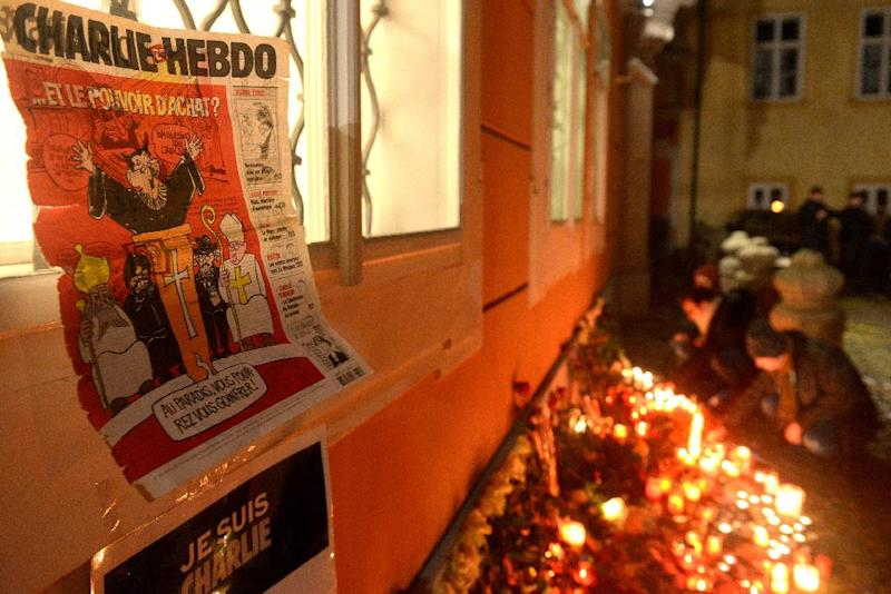 A cover of an old issue of Charlie Hebdo hangs on the wall of the French embassy on January 8, 2015 in Prague during a rally in remembrance of the victims of the Paris attacks