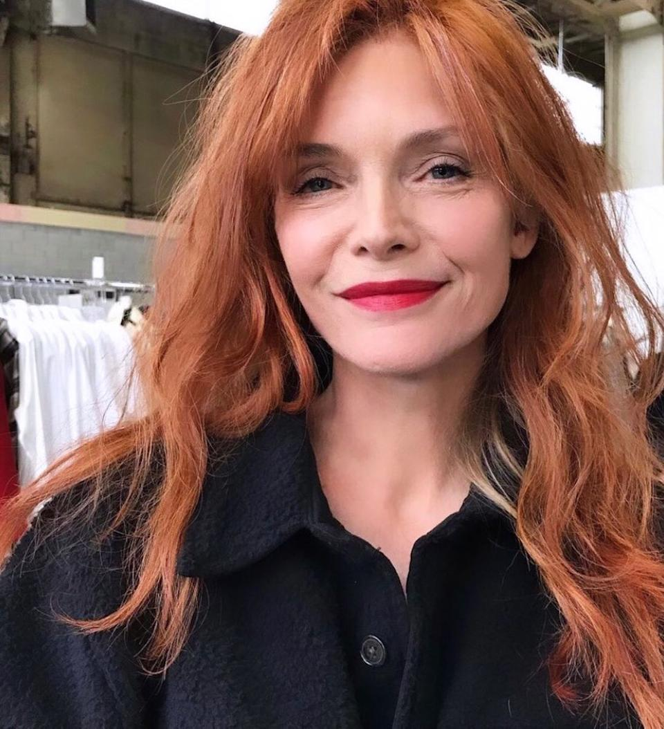 Michelle Pfeiffer with red hair wearing a black coat and red lipstick