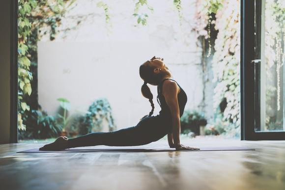 A woman holding a yoga pose in a room with large glass doors open to a leafy courtyard