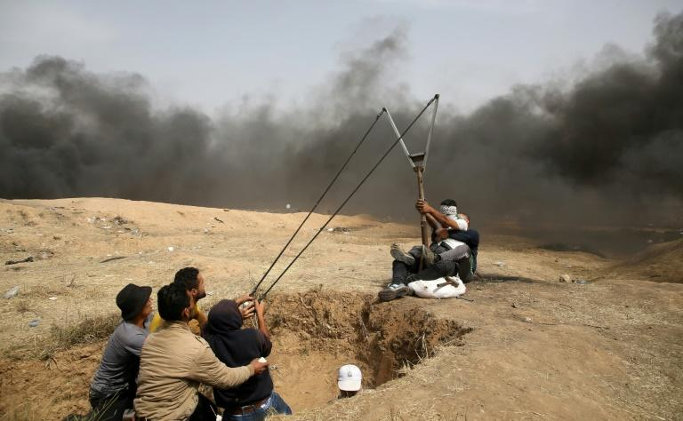 A group of Palestinian protesters man a sling to hurl stones during clashes with Israeli forces along the Gaza border