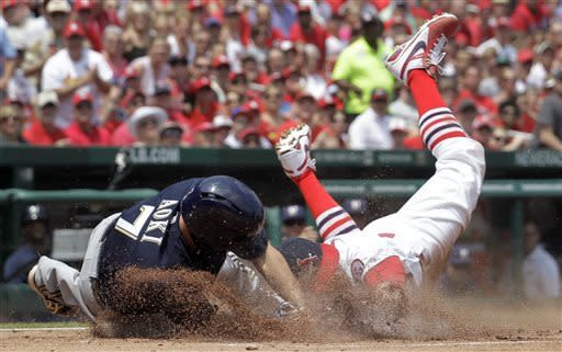 St. Louis Cardinals third baseman David Freese, right, tags Milwaukee Brewers' Norichika Aoki out at home after Aoki was caught stealing home during the first inning of a baseball game on Sunday, May 19, 2013, in St. Louis. (AP Photo/Jeff Roberson)