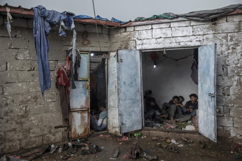 In this Aug. 4, 2019 photo, Yemenis, right, chew qat, while Ethiopian migrants, left, take shelter in a small shack at a qat market in Dhale province in Yemen. This is one of the stops where migrants take shelter to continue their journey to Saudi Arabia, and an active frontline between militiamen backed by the Saudi-led coalition and Houthi rebels only a few hundred meters (yards) away (AP Photo/Nariman El-Mofty)