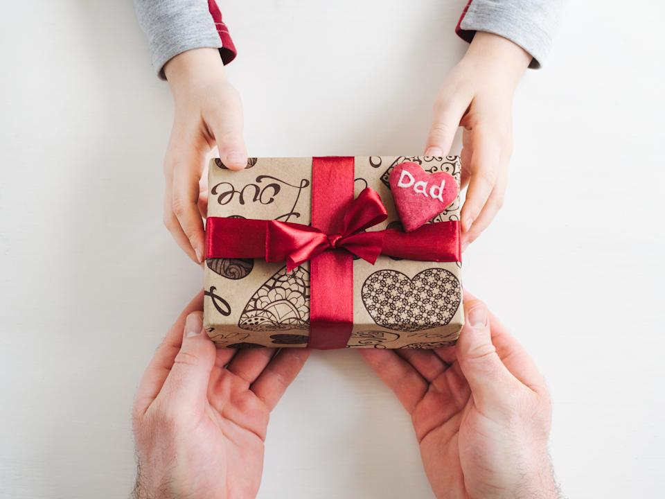 Child's hands and adult man's hands, beautiful gift box, ribbon and glazed cookies on a white, wooden background. Top view, close-up. Preparing for the holidays