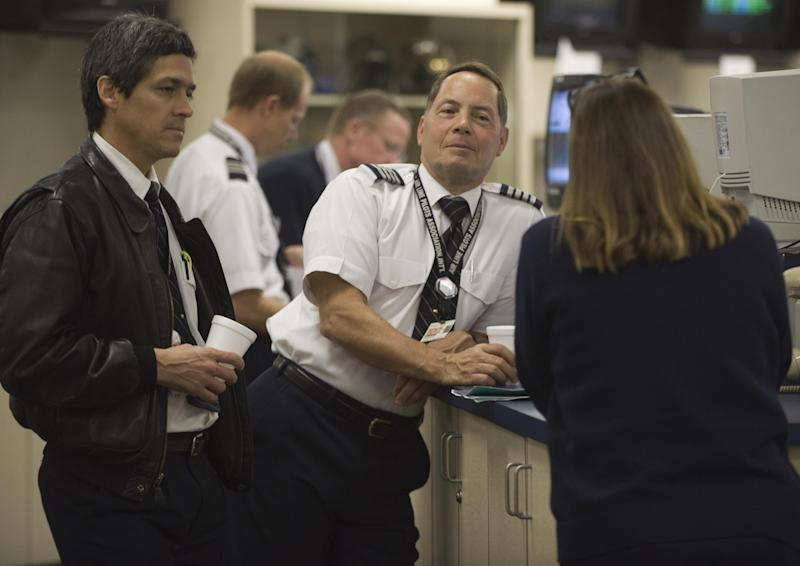 FedEx pilots relax and have a coffee as packages and documents are being loaded onto their aircraft while waiting for their flight assignments at the Memphis, Tennessee, Headquarters World Hub, where the bulk of FedEx's 675 world wide fleet of aircraft are being readied for take off, October 9, 2008. The FedEx Memphis hub is a giant operation with over 10,000 daily employees on a 727- acre facilty that processes the majority of FedEx documents moving in, out, or thru the US and then on to the destination city within a few hours. AFP PHOTO/Paul J. Richards (Photo credit should read PAUL J. RICHARDS/AFP via Getty Images)