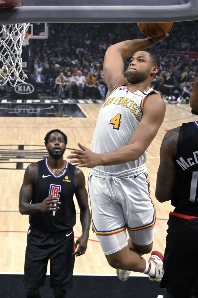 Golden State Warriors forward Omari Spellman, right, goes up for a dunk as Los Angeles Clippers forward JaMychal Green, left, watches during the first half of an NBA basketball game Friday, Jan. 10, 2020, in Los Angeles. (AP Photo/Mark J. Terrill)