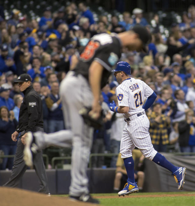 Milwaukee Brewers' Travis Shaw, right, rounds the base after hitting a solo home run off Miami Marlins pitcher Trevor Richards, foreground, during the fourth inning of a baseball game Friday, April 20, 2018, in Milwaukee. (AP Photo/Darren Hauck)