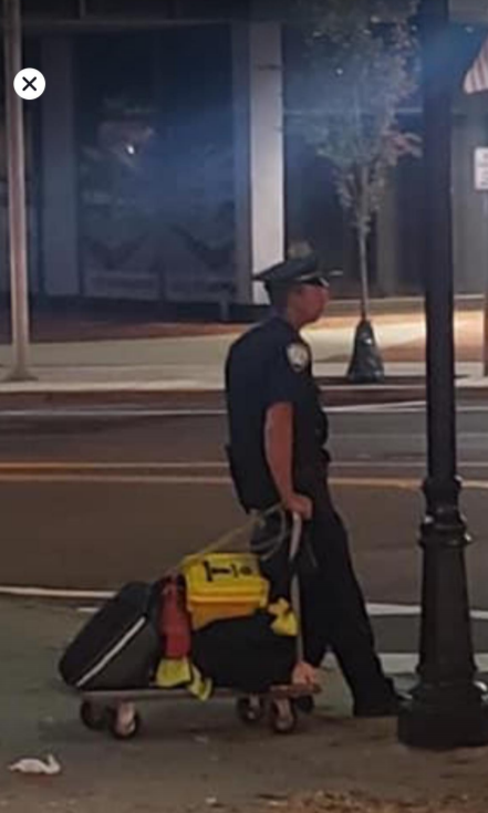 Morristown police officer Keith Hudson is seen pulling a cart with emergency equipment during a late-night walking post. The photo is cited in the PBA lawsuit filed on Monday.