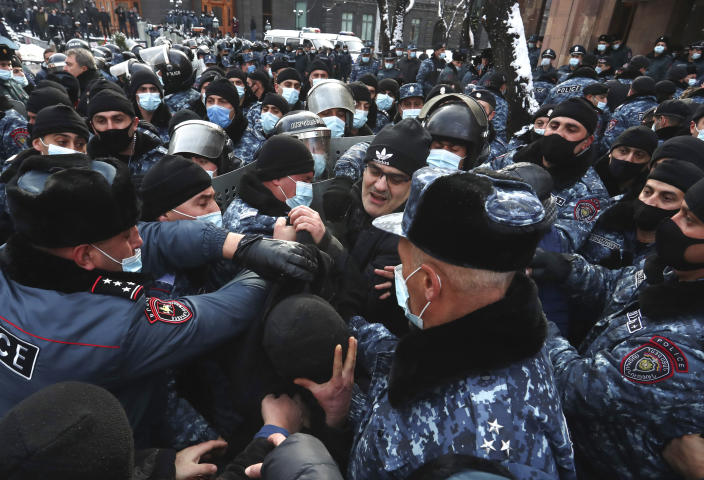 Armenian police officers detain a demonstrator during a rally to pressure Armenian Prime Minister Nikol Pashinyan to resign over a peace deal with neighboring Azerbaijan on Republic Square in Yerevan, Armenia, Thursday, Dec. 24, 2020. Armenian opposition politicians and their supporters have been protesting for weeks, demanding the prime minister's resignation over his handling of the Nagorno-Karabakh conflict with Azerbaijan. (Vahram Baghdasaryan, Photolure via AP)