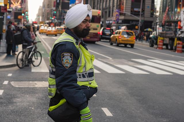 An NYPD traffic officer shown in September 2017 wearing a traditional turban directing traffic. A new settled case will allow officers to grow longer beards and wear navy blue turbans as part of their uniforms in an effort to allow more diversity in the police force. (Photo: Getty Images)