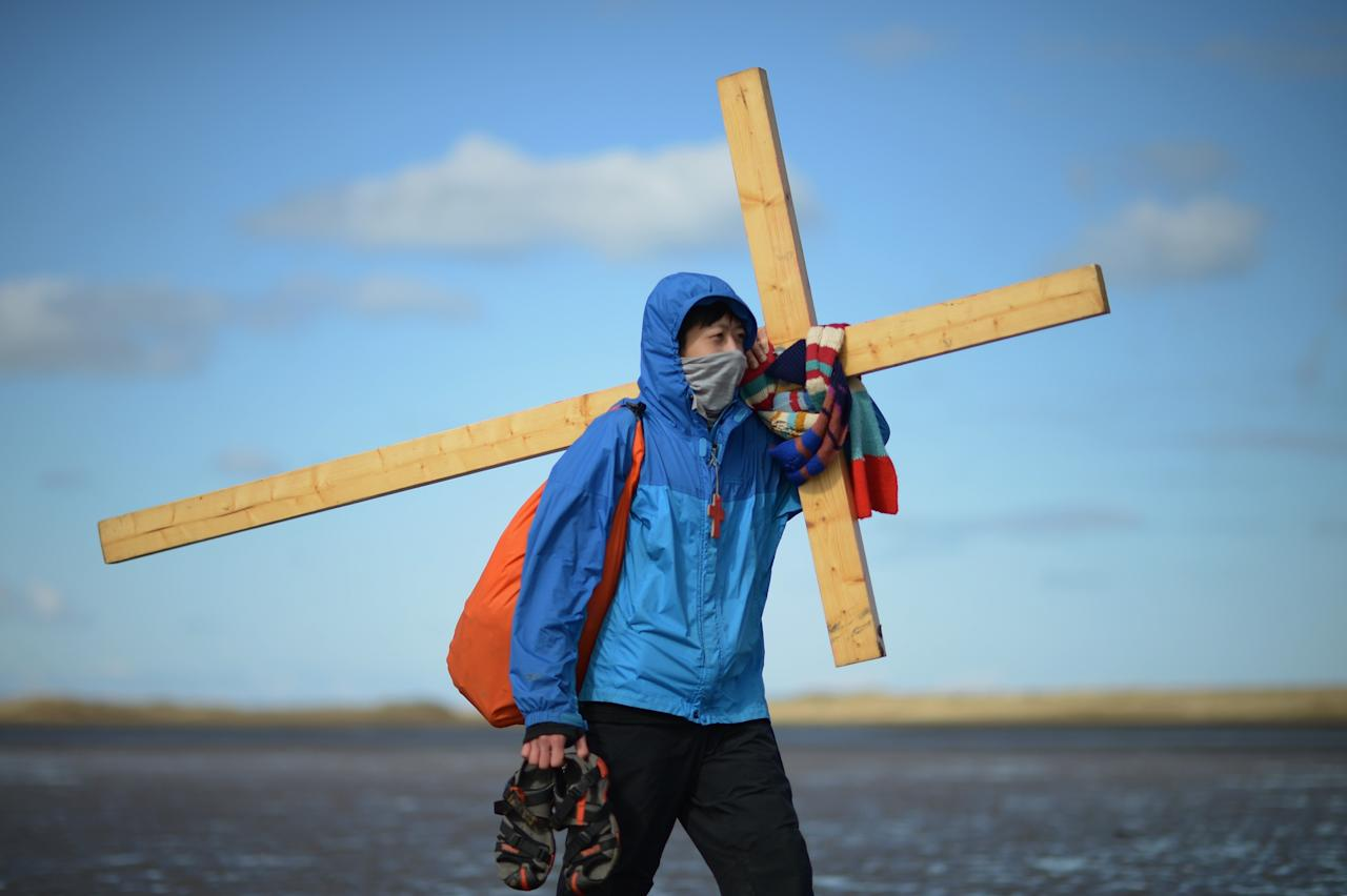 BERWICK-UPON-TWEED, ENGLAND - MARCH 29:  Pilgrims walk with crosses as the Northern Cross pilgrimage makes its final leg of the journey to Holy Island on April 29, 2013 in Berwick-upon-Tweed, England. More than 50 people, young and old, celebrated Easter by crossing the tidal causeway during the annual Christian pilgrimage. Every year people of all ages, from all over the world and from all realms of Christian life walk together at Easter to Holy Island.  (Photo by Jeff J Mitchell/Getty Images)