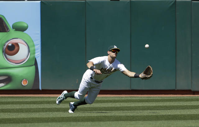 Oakland Athletics left fielder Chad Pinder catches a fly ball hit by Texas Rangers' Shin-Soo Choo during the fifth inning of a baseball game in Oakland, Calif., Wednesday, April 24, 2019. (AP Photo/Jeff Chiu)