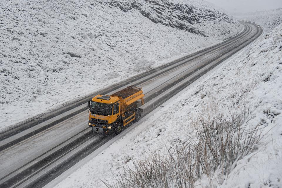 A gritter lorry spreads grit on the A62 as snow falls above the village of Delph, near Manchester in northern England on December 4, 2020. (Photo by Oli SCARFF / AFP) (Photo by OLI SCARFF/AFP via Getty Images)