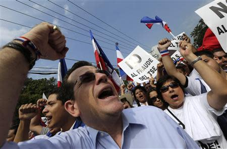 A supporter of Norman Quijano, presidential candidate of the conservative Nationalist Republican Alliance party (ARENA), shouts as others carry placards during a protest regarding alleged electoral fraud near the Supreme Electoral Court in San Salvador March 11, 2014. REUTERS/Henry Romero