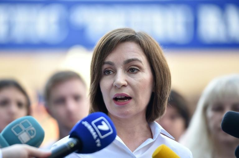 Moldovan President Maia Sandu speaks with journalists outside a polling station during parliamentary elections in Chisinau
