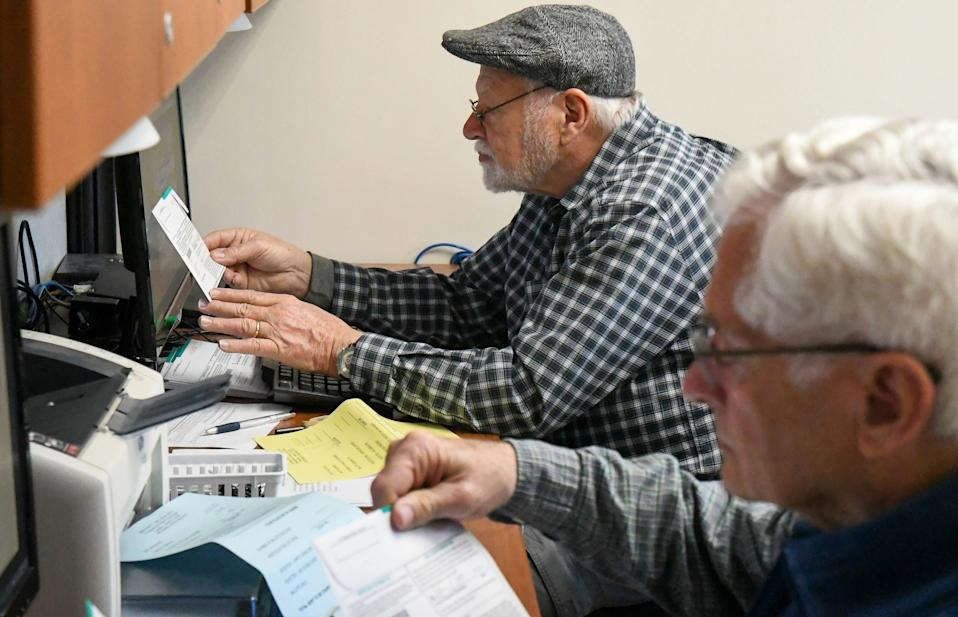 John Gorman and Eddie Piker verify ballot signatures at the Garfield County Courthouse in Glenwood Springs, Colo., on March 3, 2020, for the Super Tuesday primary elections.