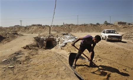 A tunnel worker shovels sand outside a smuggling tunnel on the border between Egypt and the southern Gaza Strip