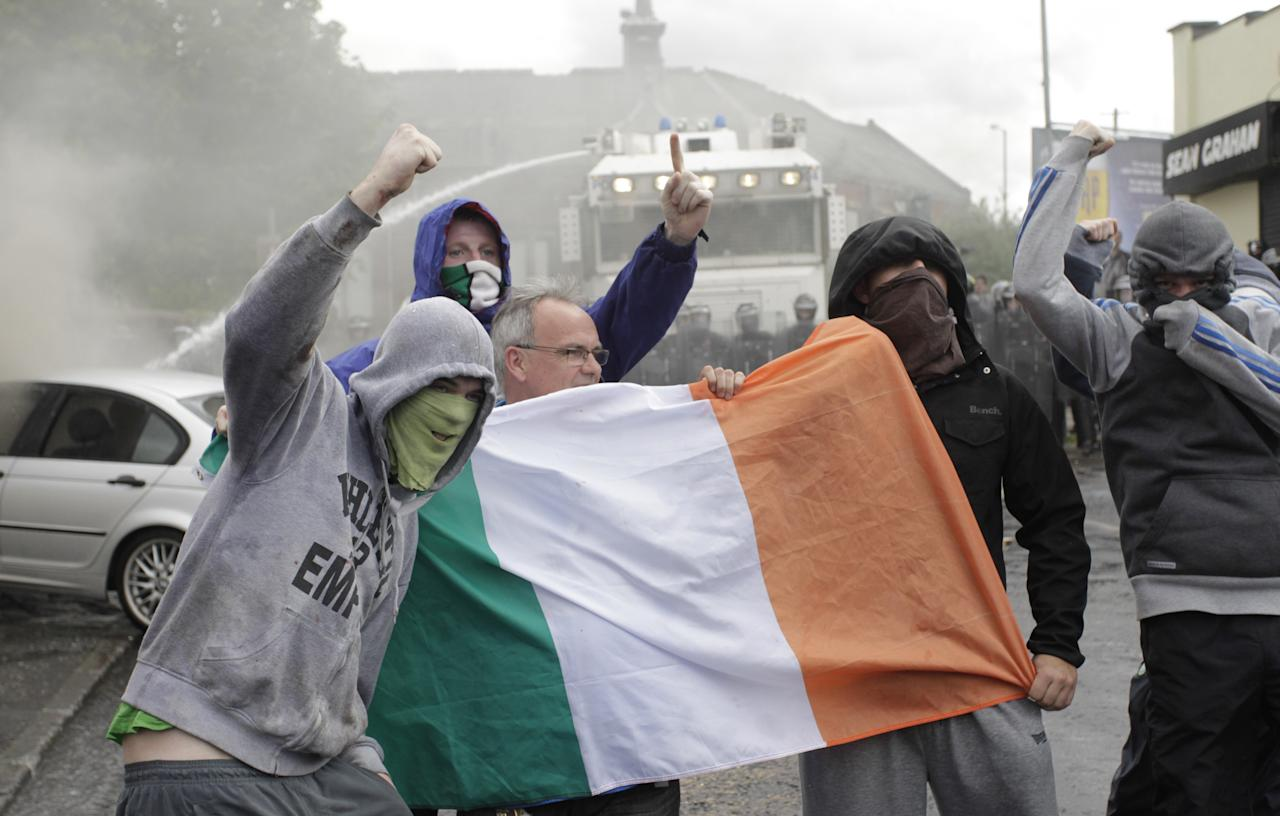 Nationalist rioters hold the Irish flag in North Belfast, Northen Ireland, Thursday, July 12, 2012. Trouble broke out after an Orange Order march passed the area. The Twelfth of July is the busiest day of the marching season in Northern Ireland with thousands of Orangemen and women, accompanied by marching bands, taking part in hundreds of parades.The Orange Order holds its main Belfast event, which commemorates King William III's 1690 Battle of the Boyne victory over Catholic King James II. (AP Photo/Peter Morrison)